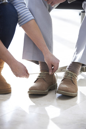 getting together: Adult Daughter Helping Senior Tie Shoelaces Stock Photo