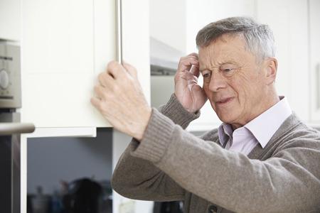 Olvidadizo hombre mayor que parece en el armario