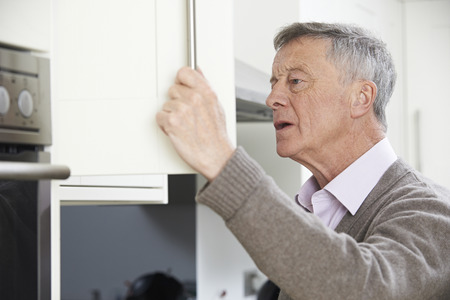one senior adult man: Forgetful Senior Man Looking In Cupboard