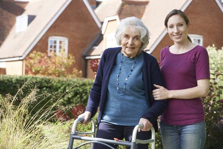 Dochter helpen senior moeder te gebruiken looprek Stockfoto