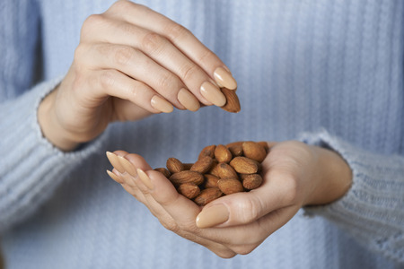 almond: Close Up Of Woman Holding Handful Of Almonds
