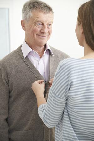 senior adult man: Adult Daughter Helping Senior Man To Button Cardigan