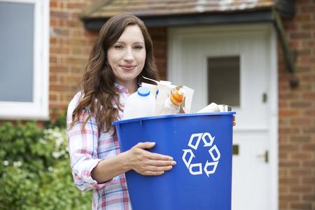 women smiling: Portrait Of Woman Carrying Recycling Bin