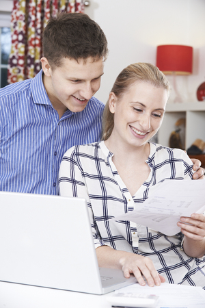 home finances: Smiling Couple Discussing Domestic Finances At Home Stock Photo
