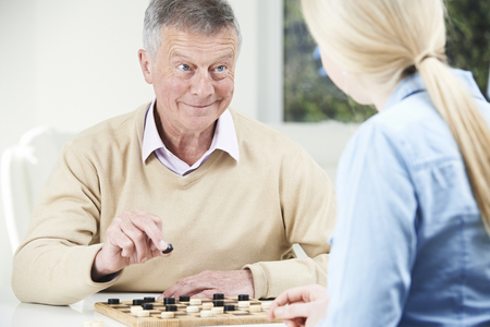 checkers: Senior Man Playing Checkers With Teenage Daughter