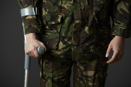 wounded: Studio Shot Of Wounded Soldier Using Crutch