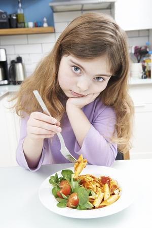 niña comiendo: Retrato de la niña no disfruta de la comida saludable en el hogar