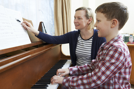 piano lesson: Boy With Music Teacher Having Lesson At Piano Stock Photo