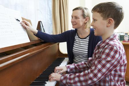 Boy With Music Teacher Having Lesson At Piano Archivio Fotografico