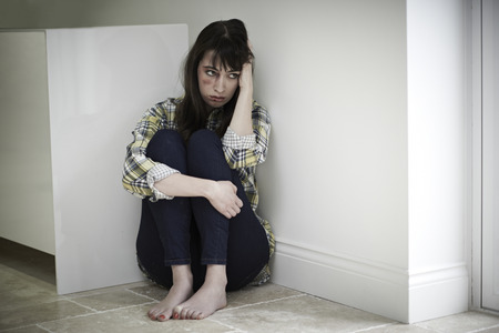 scared woman: Female Victim Of Domestic Abuse Sitting On Floor