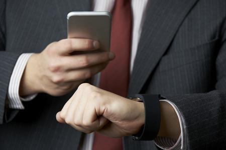 synchronizing: Businessman Synchronizing Smart Watch With Mobile Phone Stock Photo