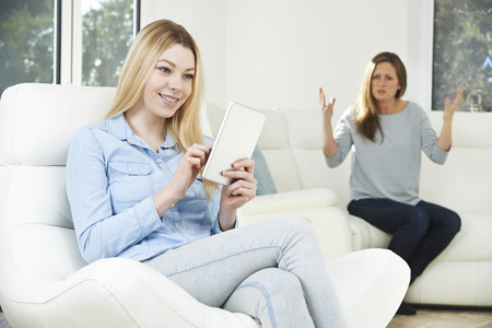 nagging: Mother Arguing With Daughter Over Use Of Mobile Phone Stock Photo