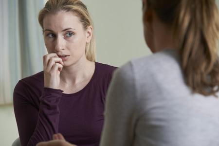 personas escuchando: Mujer joven Discutiendo Problemas con Consejero Foto de archivo