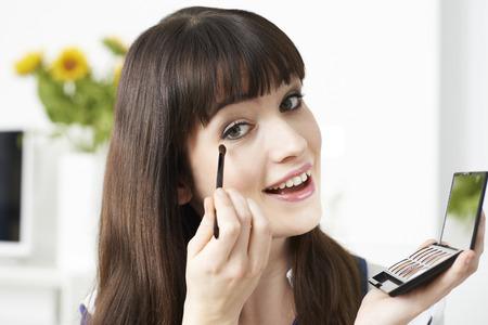 eye make up: Young Woman Applying Eye Make Up At Home Stock Photo
