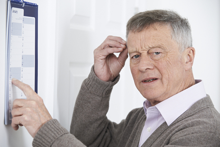 Confused Senior Man With Dementia Looking At Wall Calendar Banque d'images