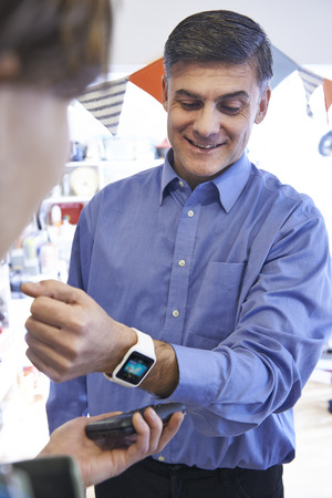 contactless: Man Using Contactless Payment App On Smart Watch In Store