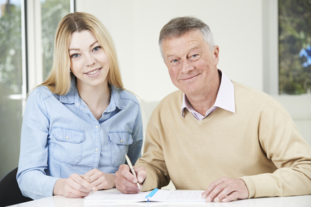 sudoku: Senior Man Playing Completing Sudoku Number Puzzle With Teenage Granddaughter Stock Photo