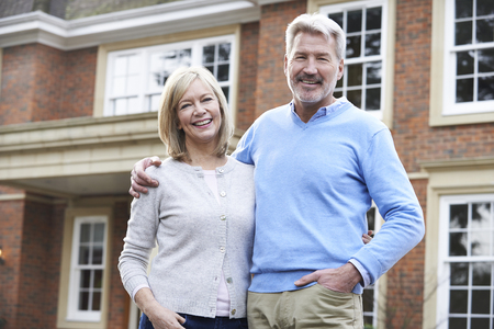 middle aged man: Portrait Of Mature Couple Standing Outside Home