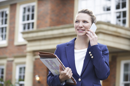 Female Realtor On Phone Outside Residential Property Archivio Fotografico