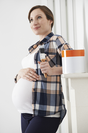 whilst: Pregnant Woman Taking Break Whilst Decorating Nursery Stock Photo