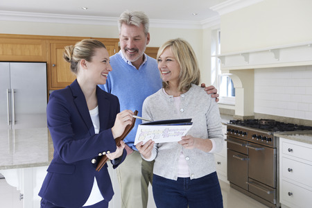 Female Realtor Showing Mature Couple Around House For Sale