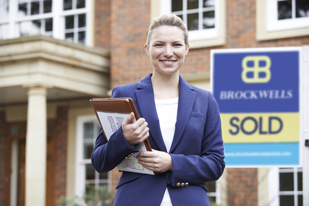 selling house: Portrait Of Female Realtor Standing Outside Residential Property