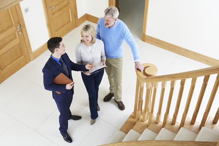 property ladder: Realtor Showing Mature Couple Around House For Sale