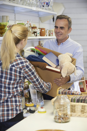 thrift store: Man Donating Unwanted Items To Charity Shop