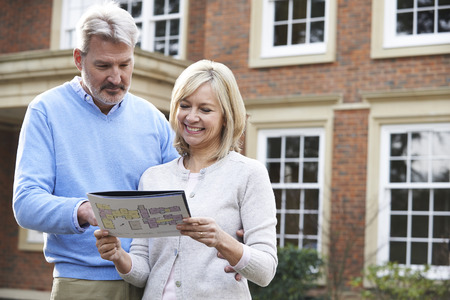 viewing: Mature Couple Standing Outside House Looking At Property Details Stock Photo