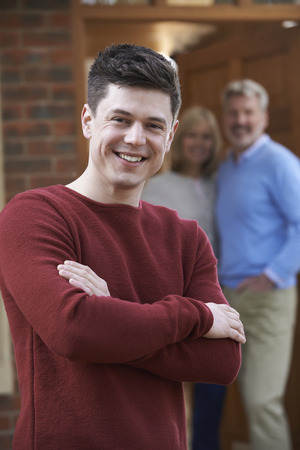 parent: Portrait Of Young Man With Parents At Home