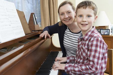 tutor: Boy With Music profesor que tienen la lección Al Piano Foto de archivo