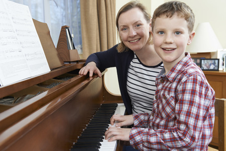 Boy With Music Teacher Having Lesson At Piano Фото со стока