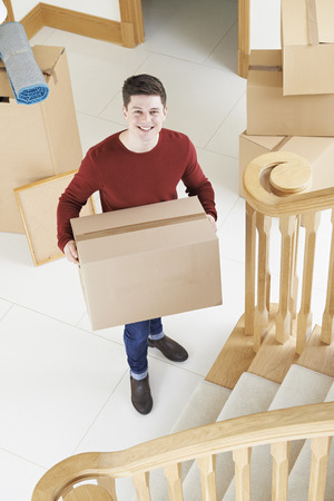 property ladder: Portrait Of Young Man Moving Into New Home