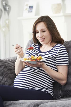 comiendo frutas: Ensalada de embarazo de la mujer que come la fruta sana Foto de archivo