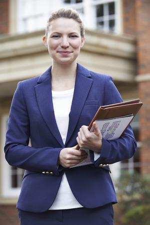 property ladder: Portrait Of Female Realtor Standing Outside Residential Property
