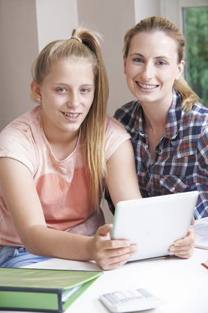 boy 12 year old: Female Home Tutor Helping Girl With Studies Using Digital Tablet