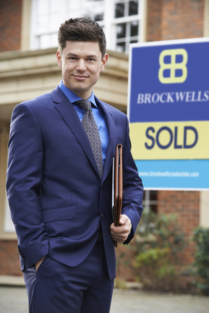 property ladder: Portrait Of Male Realtor Standing Outside Residential Property Stock Photo