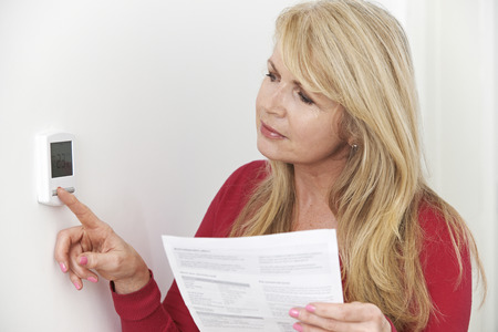 bills: Worried Woman With Heating Bill Turning Down Thermostat Stock Photo