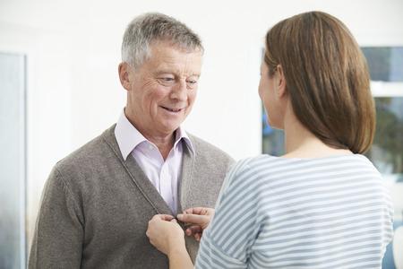 vistiendose: Hija Adulto que ayuda al hombre mayor a Cardigan Botón Foto de archivo