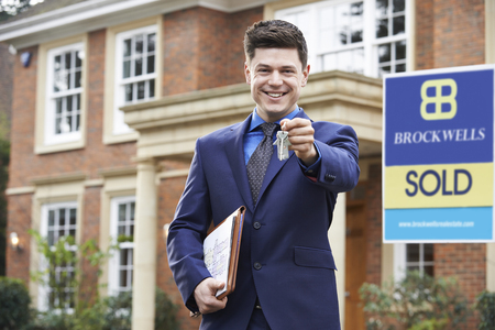 vacant sign: Male Realtor Standing Outside Residential Property Holding Keys