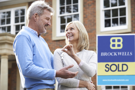 property ladder: Mature Couple Happy At Getting Keys To New House