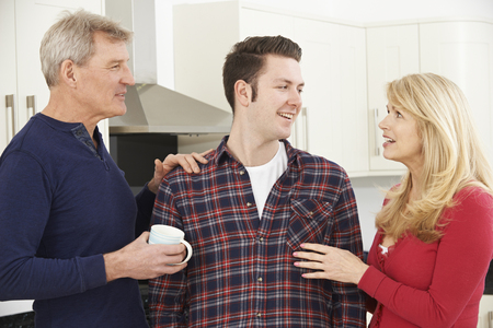 grown ups: Portrait Of Family With Adult Son At Home Stock Photo