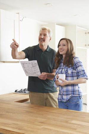 bespoke: Woman With Carpenter Looking At Plans For New Kitchen
