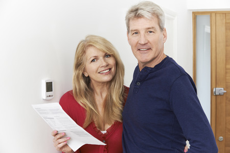heat: Mature Couple Saving Money On Domestic Heating Bills Stock Photo