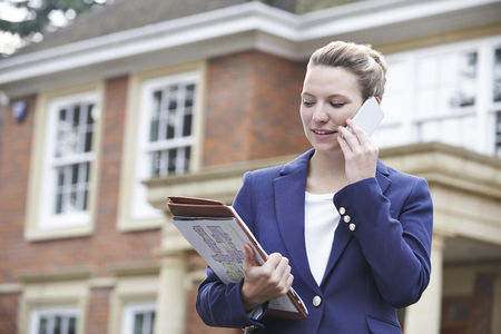 property ladder: Female Realtor On Phone Outside Residential Property Stock Photo
