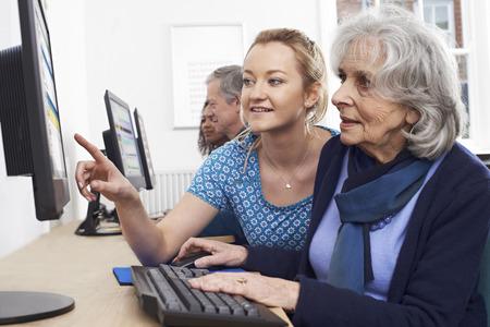 clase media: Profesor particular a la mujer mayor en clase del ordenador