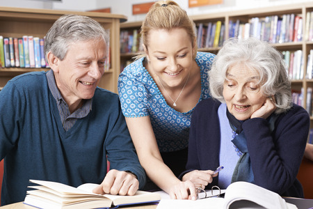 fifties: Mature Students Working With Teacher In Library Stock Photo