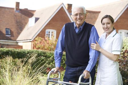 歩行車を使用して庭を散歩する年配の男性を支援介護