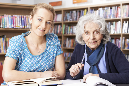 the elderly tutor: Senior Woman Working With Teacher In Library