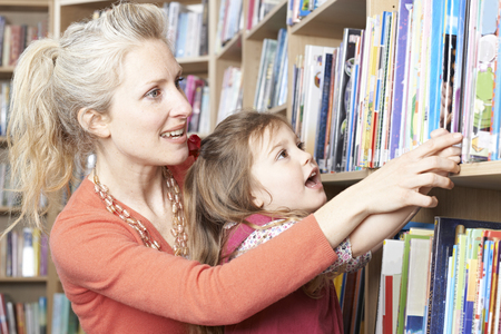 library book: Mother And Daughter Choosing Book From Library Shelf Stock Photo